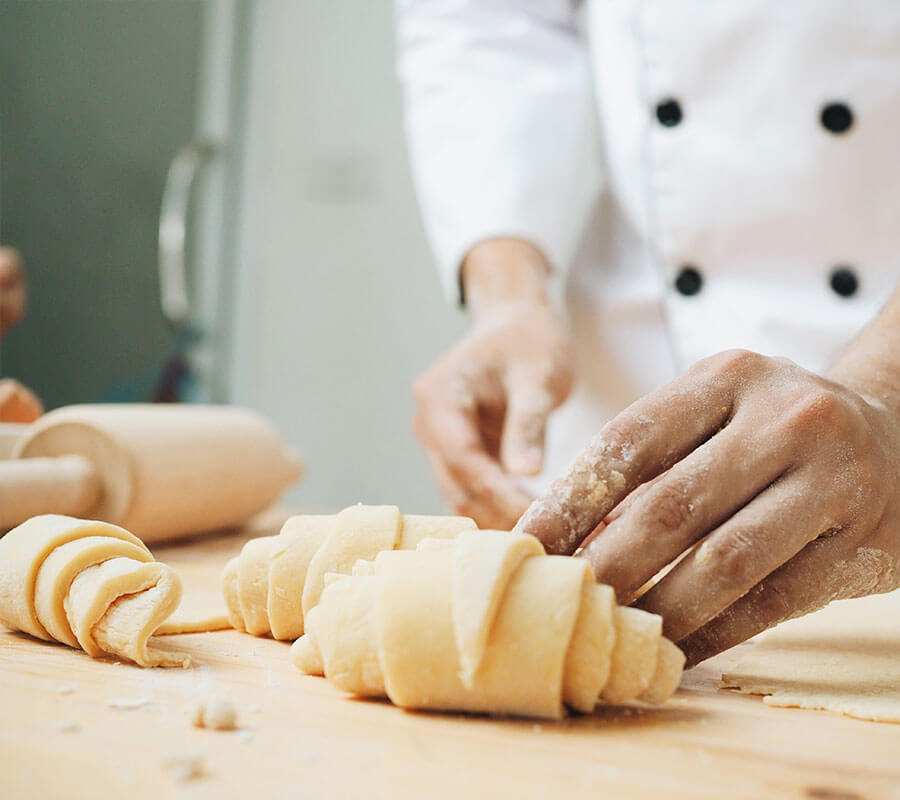 a chef rolling croissants